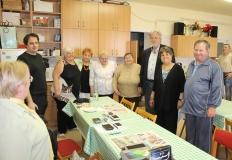 Közös kép az egyesület tagjai és a Labrador KFT munkatársaival, körül állják az asztalt.