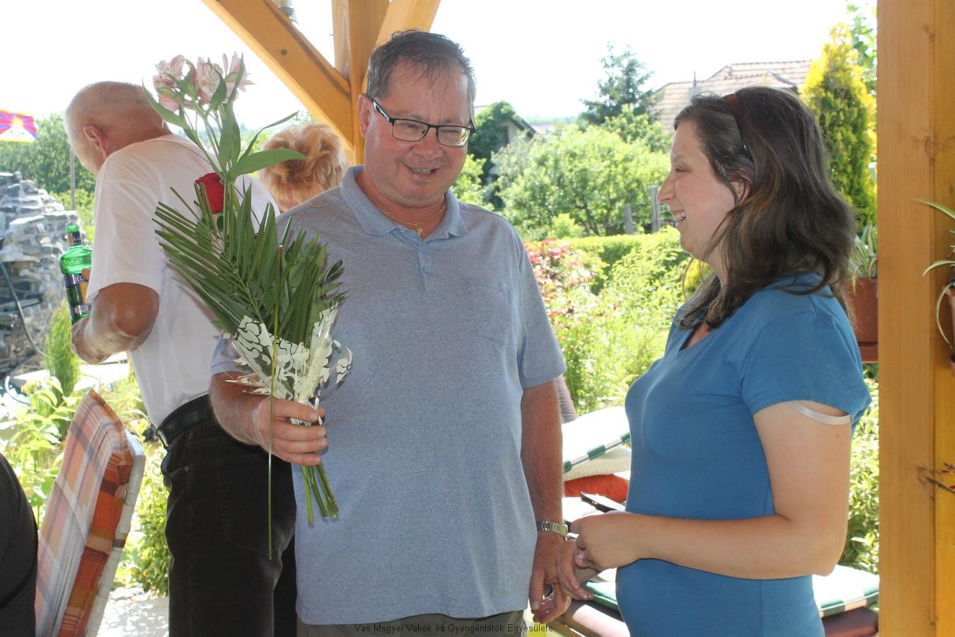 Horváth József köszönti a háziasszonyt rózsával.