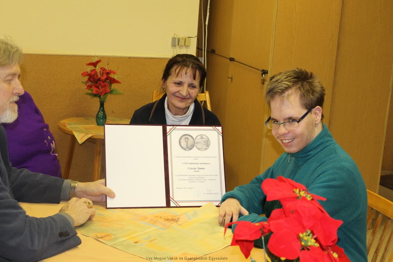 Márkus Árpád, Imre Marianna és Csiszár Tamás az oklevéllel. A képen mosolyognak. Előkerültek az iskolai történetek is a beszélgetés közben.