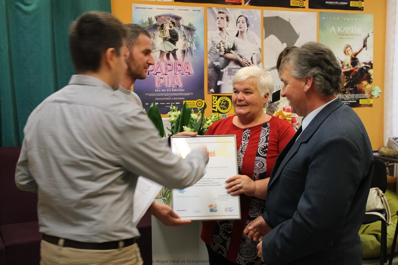 Bősze György elnök úr és Kopcsándiné Zsuzsa irodavezető átveszi az oklevelet.