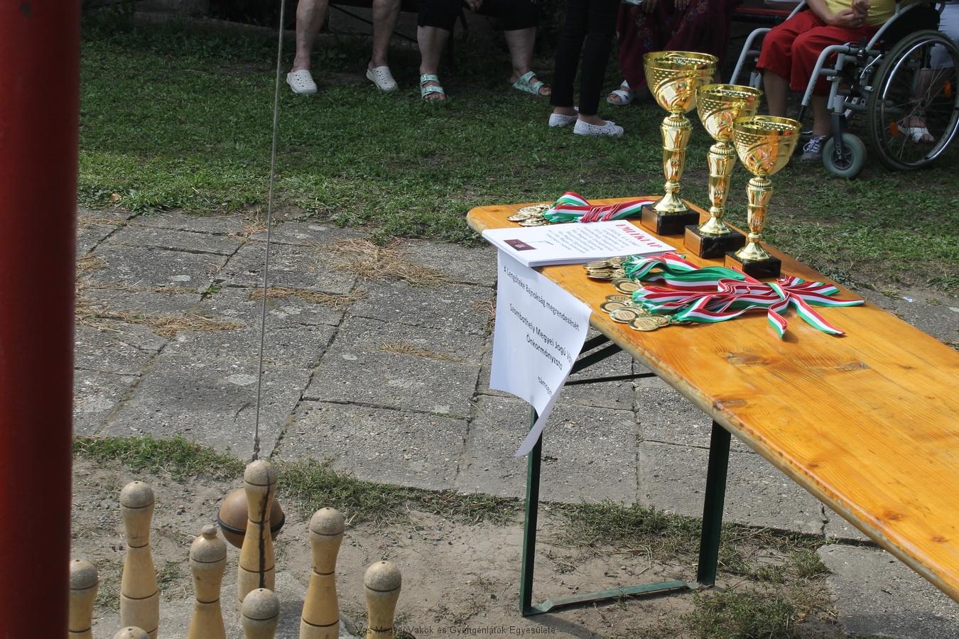 Gyülekezés a lengőteke bajnokságra. Az asztalon serlegek, oklevelek, érmek.