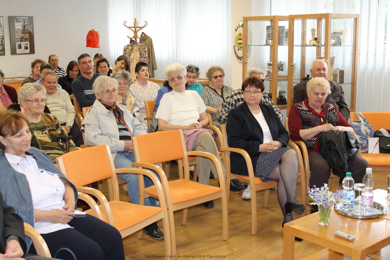 A kép jobb oldalán Nagy Lászlóné Marika alelnök asszony ül. Ő képviselte a Vakok és Gyengénlátók Vas Megyei Egyesületét. A képen még sokan láthatók, akik érdeklődéssel hallgatják az előadást.