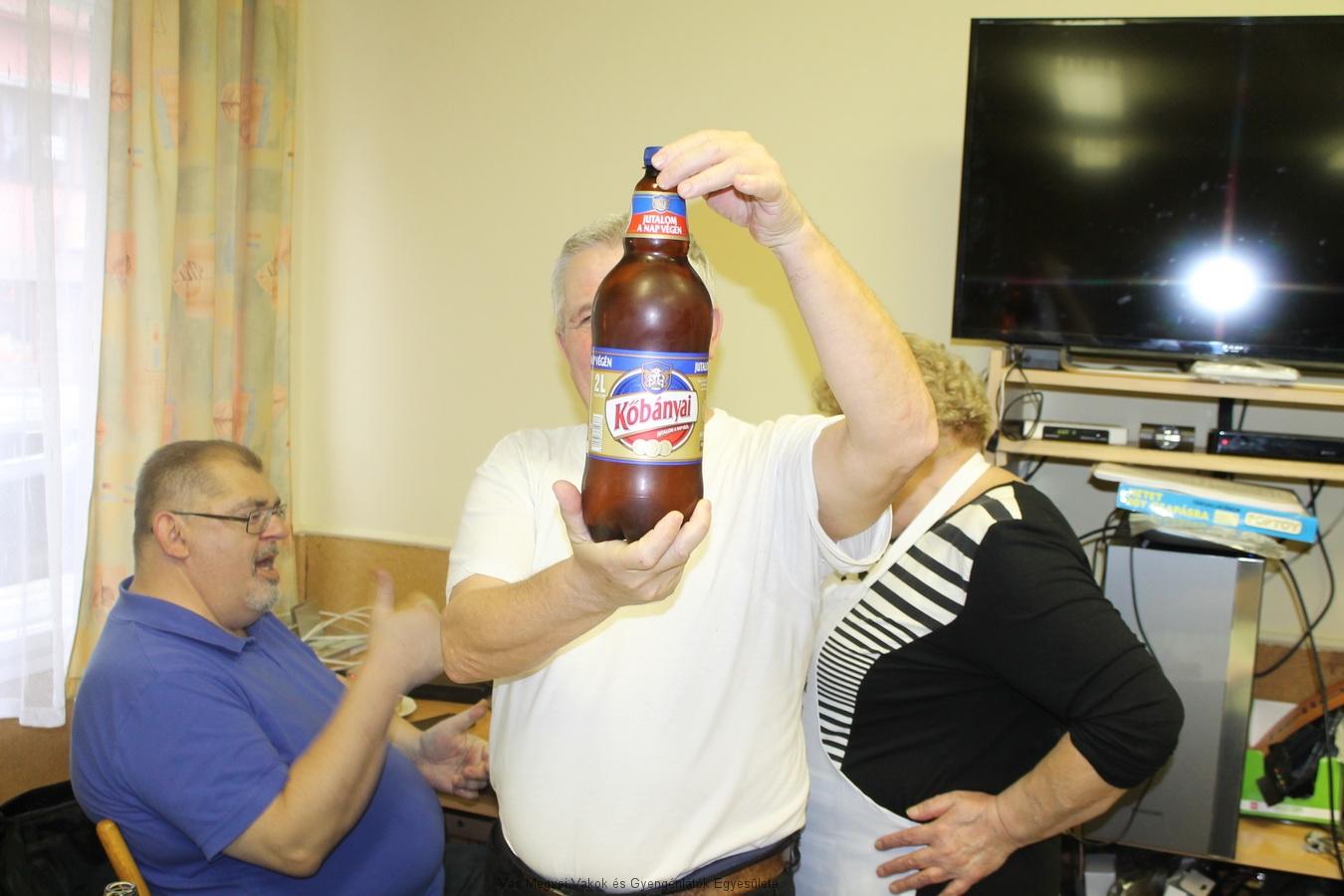 Vajda Laci kezében a nagy Kőbányais üveg. A háttérben Miklós magyaráz Nagyné Marikának.