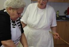 Miközben Nagyné Marika dagasztja a fánktésztát, Verácska arról beszél, mitől lesz igazán jó a fánk. Kezében nagy fakanalat tart. Ezzel verik majd a tésztát.