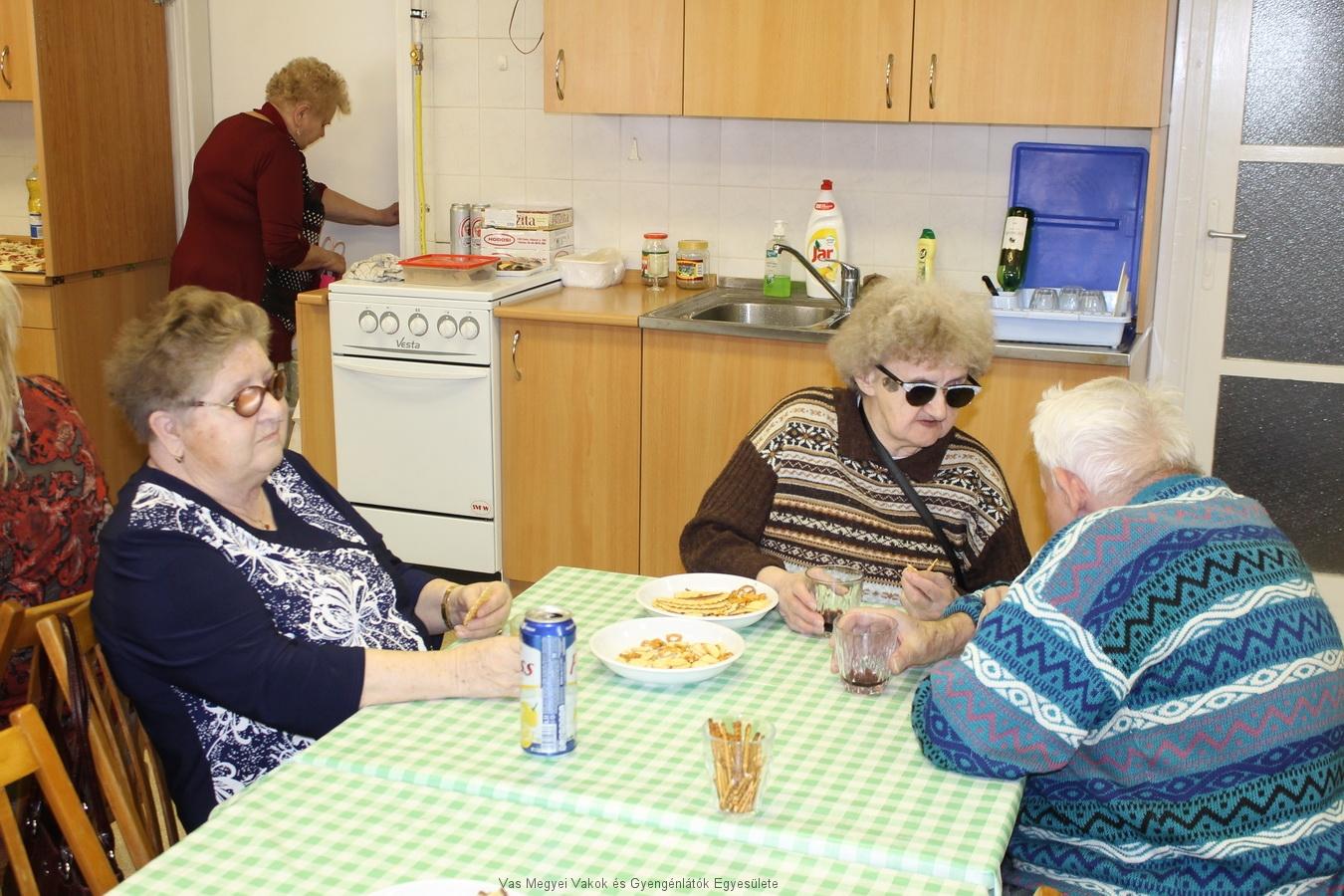 Feketéné Terike, Béla és Irénke ülnek az asztalnál, beszélgetnek és nasit esznek. A háttérben Nagyné Marika megy be a raktárba