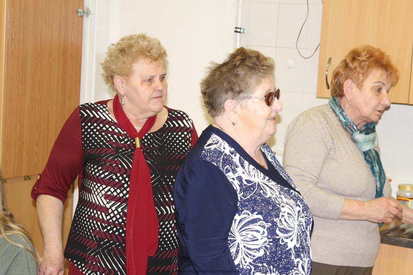 Feketéné Terike saját versét mondja. Mellette a két Marika, Kissné és Nagyné állnak.