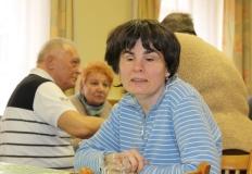Kertészné Vargyas Réka ül az asztalnál. A háttérben Goda István, Kissné Marika és Csider Sándor beszélgetnek.