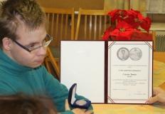 Csiszár Tamás az oklevelét és az érmét mutatja.