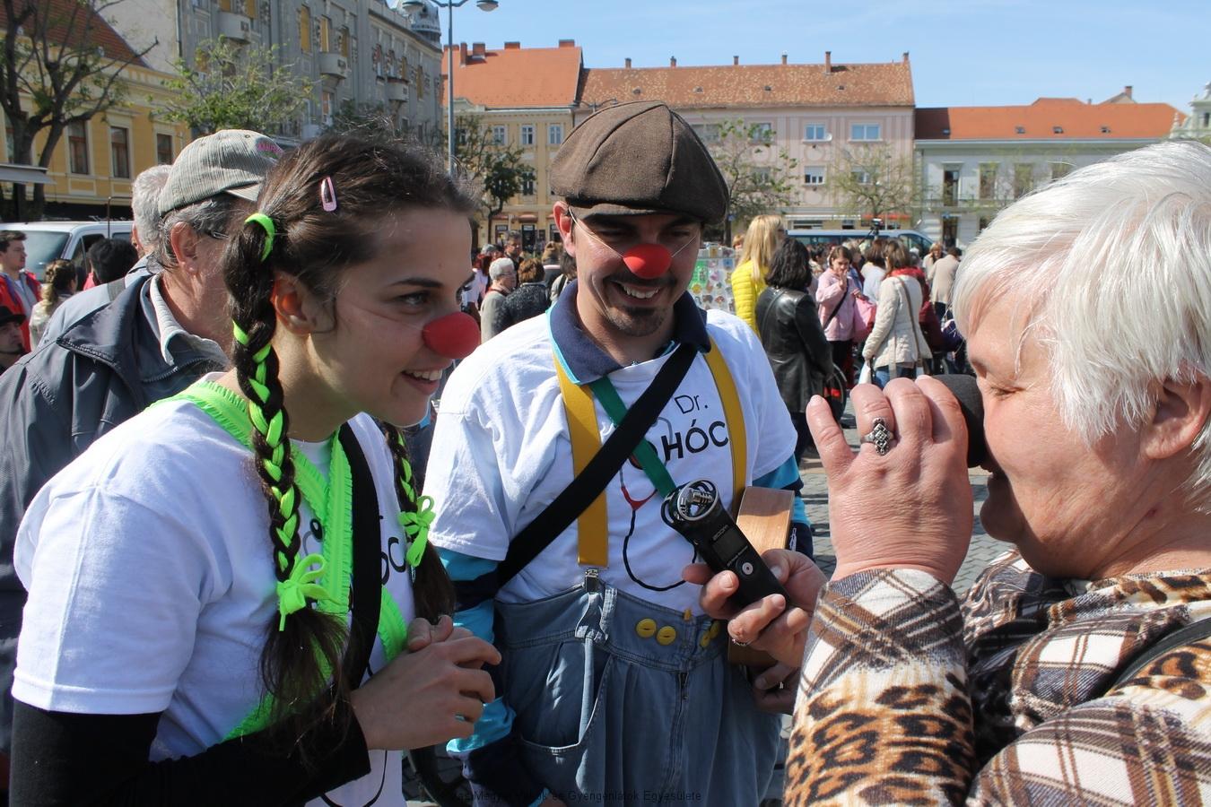 A háttérben Horváth József, előtérben a bohócdoktorok a Kopcsándiné Zsuzsa orrára próbálják a bohóc orrot.