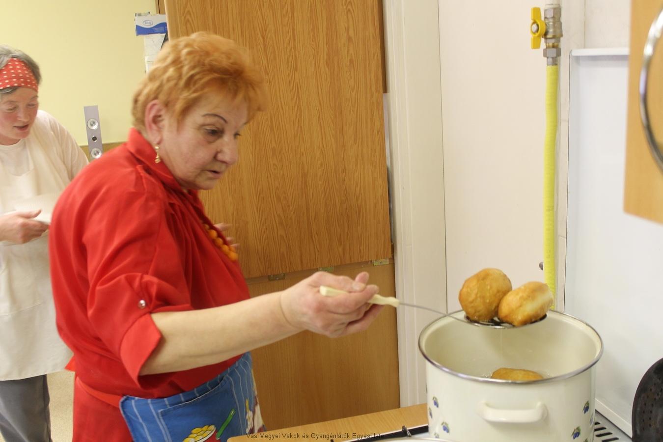 Kissné Marika a fánkokat szedi ki a forró olajból. Szép szalagosak lettek a fánkok. Háttérben Verácska látható.