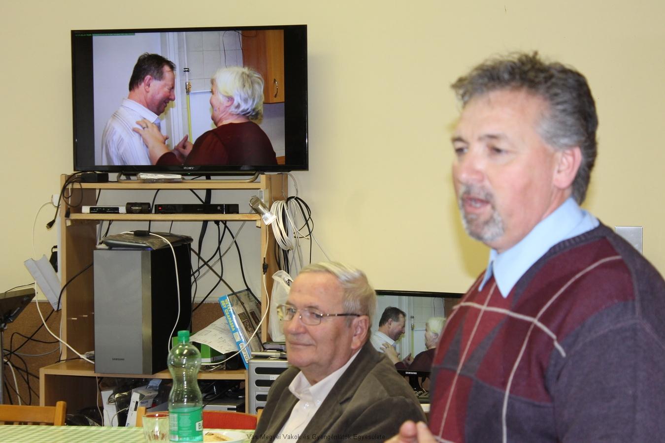 Bősze György, jelenlegi elnök, megnyitja az ünnepséget. Csider Sándor ül az asztalnál. Háttérben a TV-n Kopcsándi Gyula által készített korábbi kép látható, Kopcsándiné Zsuzsa és Horváth József táncolnak.